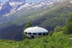 People around UFO that landing between caucasus mountains - stock photo