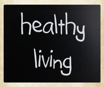"""Healthy living"" handwritten with white chalk on a blackboard - stock photo"
