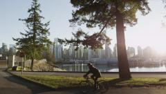 Slomo - Vancouver Skyline Sunset Park Cyclist - 01 Stock Footage