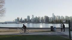 Slomo - Vancouver Skyline Sunset Park Cyclist - 02 Stock Footage