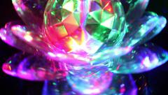Spinning crystal lotus flower LED light at night Stock Footage