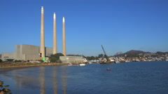 Smokestacks from a power plant tower over Morro Bay, California. Stock Footage