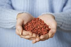 Close Up Of Woman Holding Handful Of Goji Berries Stock Photos