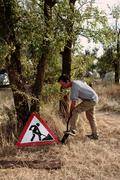 "man digging near the sign ""forbidden to dig"" - stock photo"