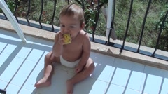 Baby eats corn then throws it away - stock footage