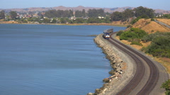 An Amtrak train passes along a shoreline in the Bay Area of California. - stock footage