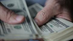 Hands of an old man counting hundred dollar bills at a table - stock footage