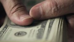 Close up of hands of an old man counting hundred dollar bills at a table - stock footage