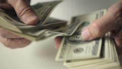 Hands of an old man counting hundred dollar bills at a table. Slow motion Stock Footage