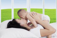 Attractive mother kissing her child on bed - stock photo