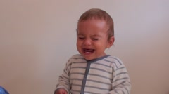 Crying child against white wall Stock Footage