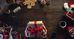 Top view hands holding christmas presents at wooden desk from above - Red Epic Stock Footage