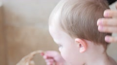 A mother cuts her little boys hair Stock Footage