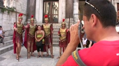 Fake Roman soldiers and a tourist taking pictures Stock Footage