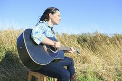 Country hippie girl with guitar at wheat field drinking black ca Kuvituskuvat