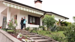 Middle aged couple posing in front of their villa Stock Footage