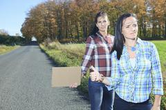Two Womans asking for a hitch hicking on the road Stock Photos