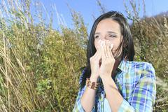 Stock Photo of A Young woman sneezing in a field. Concept: seasonal allergy