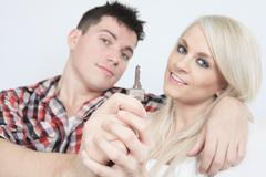 Close-up of a young couple receiving their new car's key sitting Stock Photos
