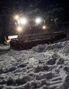 Snowcat preparing a slope in mountains Stock Photos