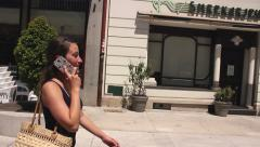 Nice girl walking in the city under the sun and talking on the phone happy Stock Footage