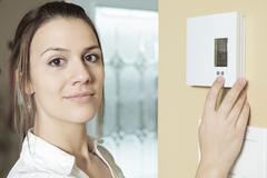 A woman set the thermostat at house Stock Photos
