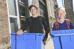 Two kids with a recycle bin outside Stock Photos
