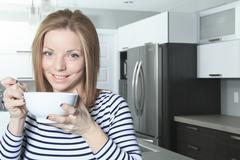 A Jolly woman having breakfast at home - stock photo
