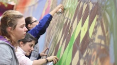 Young graffiti writers learning how to paint with colors on a wall Stock Footage