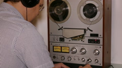 Man with headphones working with reel tape recorder Stock Footage
