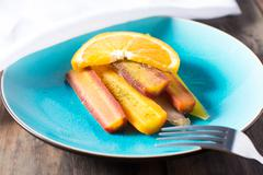 Plate of multi colored carrots with orange sauce Stock Photos