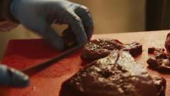 Close up butcher cutting/slicing meat/liver on slab Stock Footage