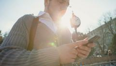 Busy businessman uses a smartphone and sunlight shine on it by the large outdoor Stock Footage