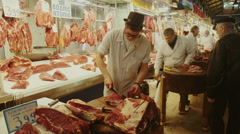 Close up,young.hip butcher cutting/slicing meat on slab Stock Footage