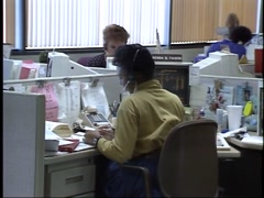 Stock Video Footage of 1990's female office workers talking on phone at desk
