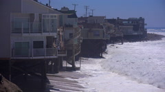 Large waves crash along a Southern California beach near Malibu endangering Stock Footage
