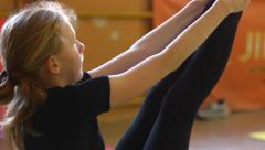 Young girl hard training in circus acrobatic troupe - stock footage