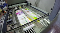 4k folding machine folds printed offset sheet as part of newspaper brochure i Stock Footage