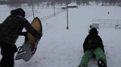 Sledding on their stomachs Stock Footage