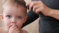 A woman cutting her little boys hair with scissors Stock Footage