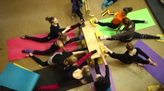 Hard training of circus acrobatic troupe - girls stretching sit on twine - stock footage
