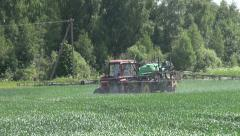 Tractor spray fertilize green crop field with pesticide insecticide herbicide Stock Footage