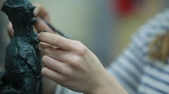 Girl's hands are sculpting a figuire of clay (close-up) Stock Footage