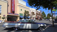 Establishing shot of a small retail business district with a classic car parked Stock Footage