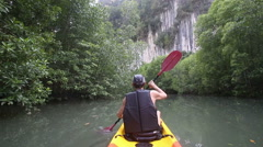 Strong elder man floats kayak to gray cliff Stock Footage