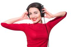 Wonderful teenager girl  listening to the music in big headphones in red clot Stock Photos