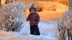 Happy beautiful little girl throws snow in winter, night lighting Stock Footage