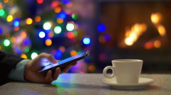 The man work with phone. By cup tea. Tree New Year and fireplace background Stock Footage
