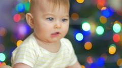 The baby look and play with toy. Close-up portrait view Stock Footage