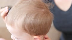 A mom cuts her little boys hair Stock Footage